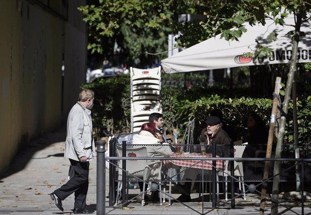 Un hombre camina frente a la terraza de un bar donde hay sentadas otras tres personas en la zona básica de salud de Guzmán el Bueno, en el distrito de Chamberí, en Madrid (España), a 26 de octubre de 2020. Guzmán el Bueno es una de las zonas básicas de sa