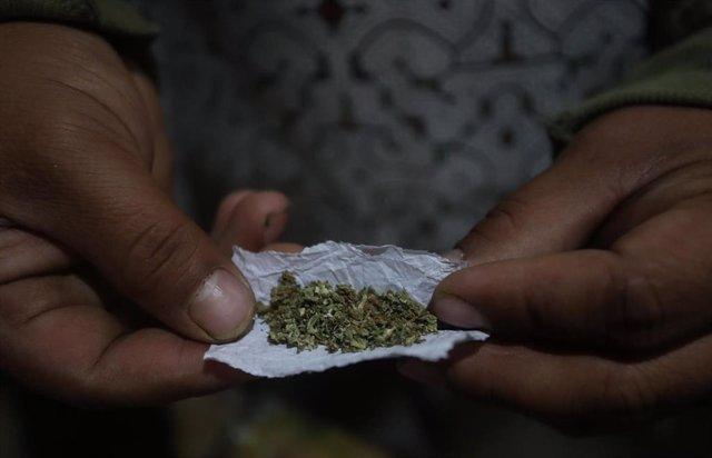 Una persona anónima muestra un cigarrillo de marihuana