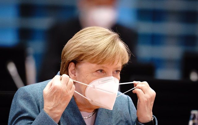 Angela Merkel quitándose la mascarilla tras llegar a una reunión en la Cancillería, en Berlín
