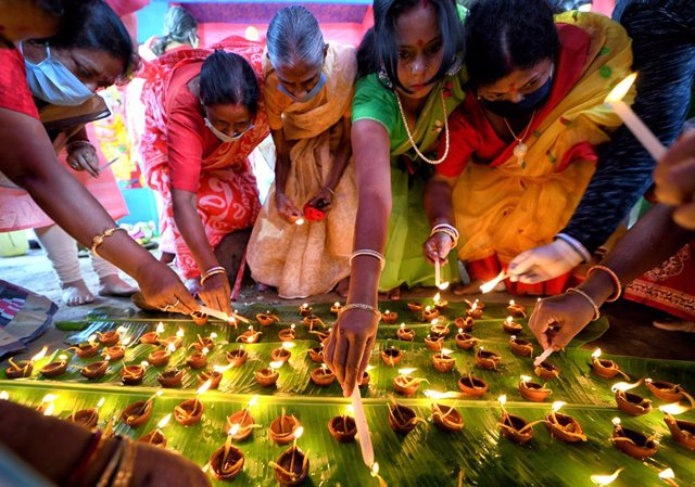 24 October 2020, India, Kolkata: Hindu devotees wear face masks as they light oil lamps, also known as Diyas, in front of Lord Durga idol during the Sandhi Puja Ritual of the Durga Ashtami festival. Photo: Avishek Das/SOPA Images via ZUMA Wire/dpa