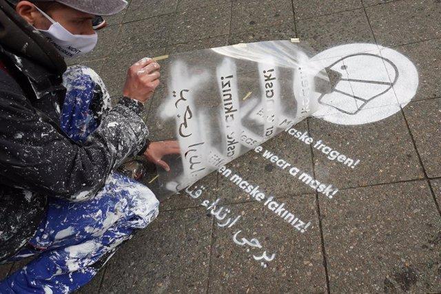 Un hombre pinta un mensaje para recordar la obligación de uso de mascarilla en Berlín
