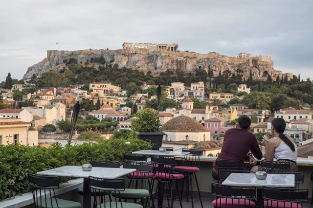 25 May 2020, Greece, Athens: Guests sit in a cafe in the Monastiraki district with the Acropolis in the background, as cafes and restaurants are allowed to reopen today after a lockdown due to the spread of the coronavirus pandemic. Photo: Socrates Baltag