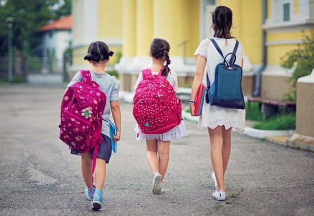 Niñas vuelven al colegio con sus mochilas a la espalda.