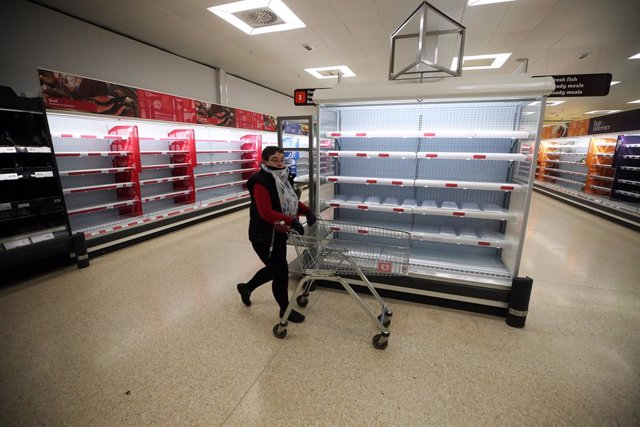 19 March 2020, England, Telford: A woman shops as empty shelves are seen at a Sainsbury, amid a wave of panic buying because of fears of the spread of Coronavirus (SARS-CoV-2). Photo: Nick Potts/PA Wire/dpa