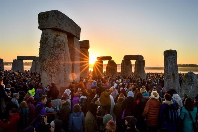 21 June 2019, England, Wiltshire: The sun rises between the stones at Stonehenge, where masses of people meet to celebrate the dawn of the longest day in the England. Photo: Ben Birchall/PA Wire/dpa
