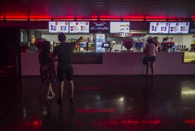 Dos personas eligen un menú de palomitas y refresco en el primer fin de semana con estrenos en las salas de cine, el pasado mes de junio