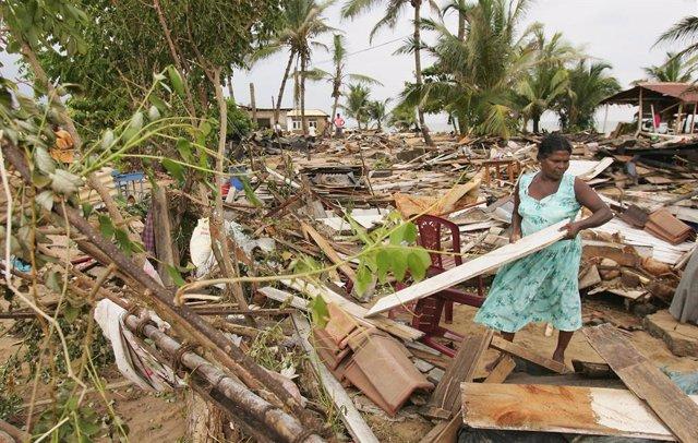 Una mujer recoge restos de los daños materiales en Sri Lanka provocados por el tsunami que azotó en 2004 a países del Océano Índico.