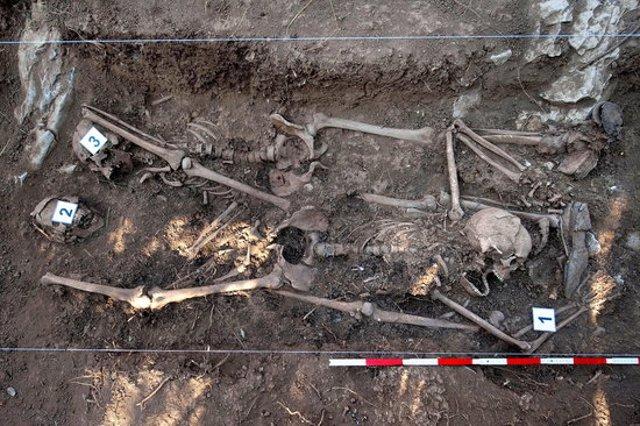 Pla mitjà picat de la fossa comuna prop de Pamplona amb tres esquelets (horitzontal).