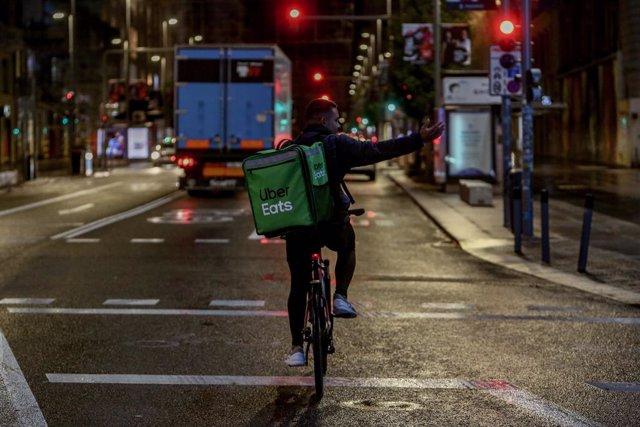 Un rider de Uber Eats circula durante la primera noche de toque de queda en Madrid (España), a 26 de octubre de 2020. El Gobierno central anunció ayer la aprobación del estado de alarma para toda España, que entró en vigor ayer mismo y que implanta un con