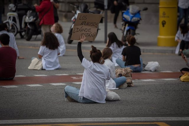 Una profesional sanitaria sostiene un cartel en el que se lee '¿Dónde están ahora los aplausos?' sentada en el suelo de la Calle de Balmes con Gran Via de les Corts Catalanes en una nueva concentración de Médicos Internos Residentes (MIR) en Barcelona, Ca