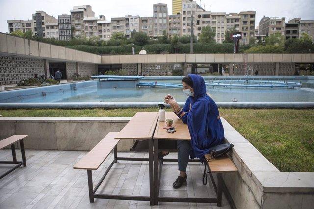 Una mujer con mascarilla en una cafetería de Teherán