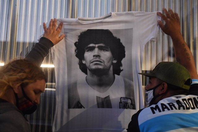 03 November 2020, Argentina, Buenos Aires: Fans of Argentine football legend Diego Maradona hold up a t-shirt with bearing his picture in front of the clinic where Maradona underwent a surgery for a bleed on the brain. Photo: Ramiro Gomez/telam/dpa