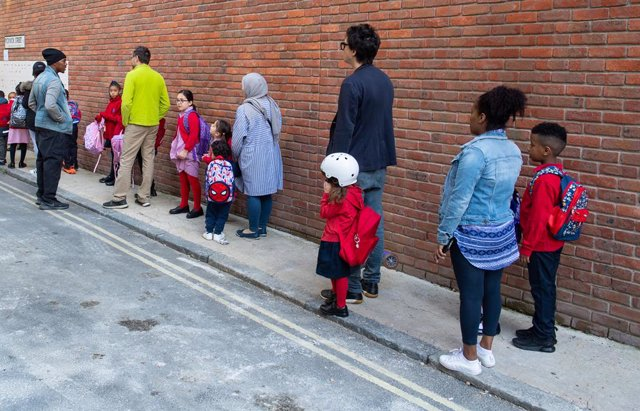 01 September 2020, England, London: Parents queue up with their children at Charles Dickens Primary School on the first day of reopening schools after closure due to coronavirus pandemic. Photo: Dominic Lipinski/PA Wire/dpa