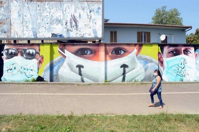 Un mural de personas con mascarillas en Milán