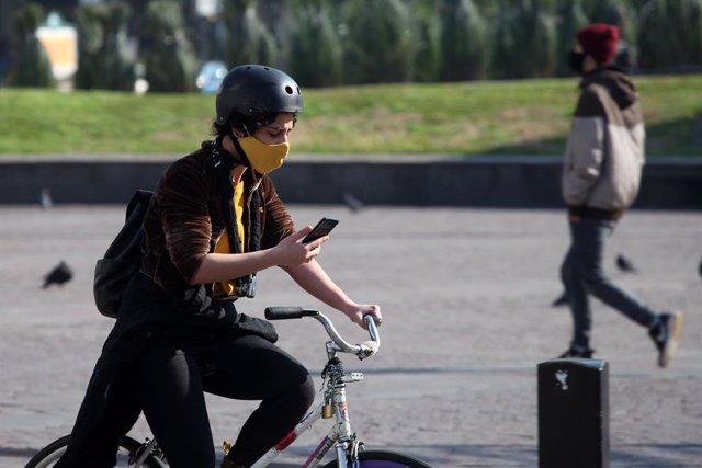 Una joven pasea en bicileta por el centro de Buenos Aires.