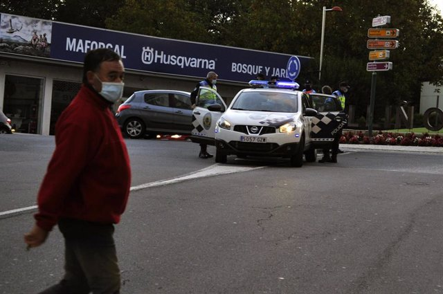 Un hombre pasa al lado de varios agentes durante un control de movilidad en una vía de O Carballiño, Ourense, Galicia (España), a 15 de octubre de 2020. Desde hoy, la Xunta limita las entradas y salidas de las localidades orensanas de Carballiño, O Irixo