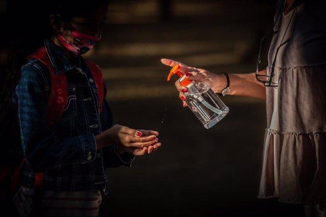 Una professora administra gel desinfectant a un alumne en un col·legi durant el primer dia del curs escolar 2020-2021, a Barcelona, Catalunya (Espanya), a 14 de setembre del 2020.