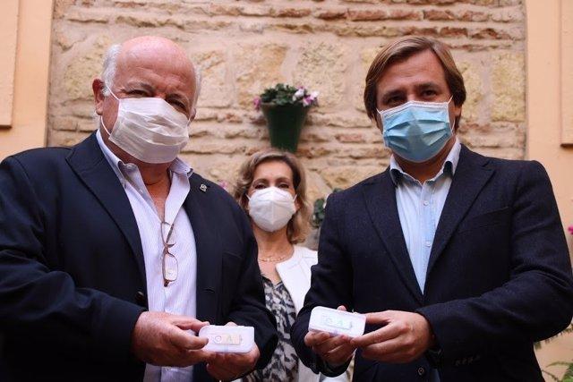 Aguirre y Repullo muetran los lápices de memoria que recogen el presupuesto andaluz para 2021.