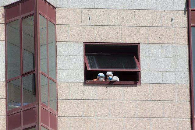 Dos trabajadores protegidos se asoman por una de las ventanas de la residencia de mayores DomusVi de Outeiro de Rei en Lugo, Galicia (España), a 8 de septiembre de 2020. La Xunta ha intervenido el geriátrico tras detectar 99 positivos más en covid-19, 94