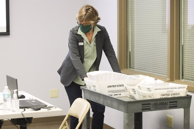 06 November 2020, US, Tampa: Peg Reese, Hillsborough County Supervisor of Elections Chief of Staff, brings in a collection of vote by mail ballots as they prepare to begin canvassing mail-in and provisional ballots at the Hillsborough Supervisor of Electi
