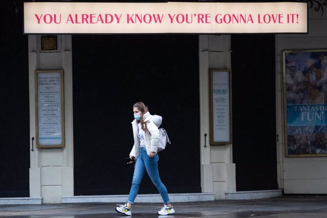 15 October 2020, England, London: A woman wearing a FACE mask walks beneath a sign outside theatre in Covent Garden. Photo: Dominic Lipinski/PA Wire/dpa