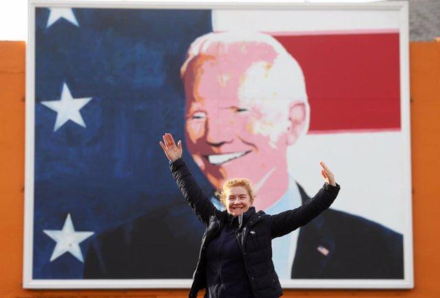 Una simpatizante de Joe Biden frente a una imagen del presidente electo de EEUU