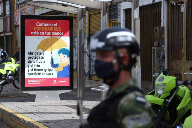01 June 2020, Colombia, Bogota: An armed and masked soldier controls access to the Kennedy neighborhood, where a strict quarantine is in place due to the increaseing number of reported Coronavirus (Covid-19). Photo: Camila Díaz/colprensa/dpa
