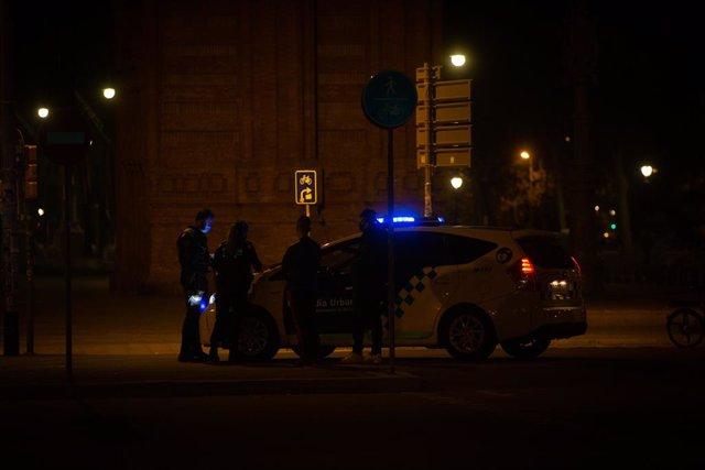 Un home signa en el capó d'un vehicle de la Guàrdia Urbana una multa per saltar-se el toc de queda.