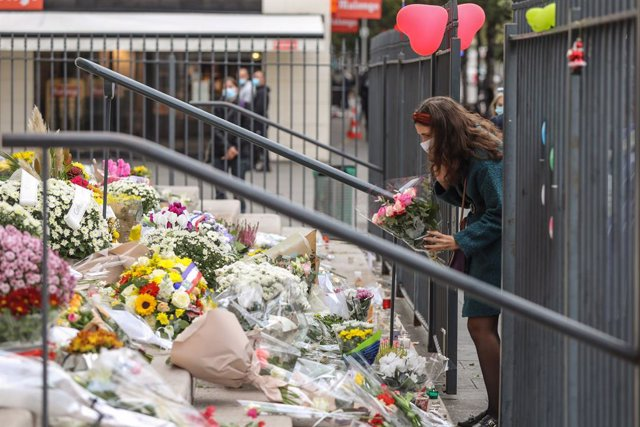31 October 2020, France, Paris: A woman lays flowers on the steps of the Basilica Notre-Dame for the victims of a knife attack in Nice. Photo: Valery Hache/AFP/dpa
