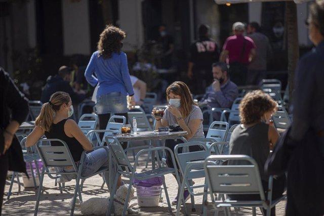 Varias personas en la terraza de un bar, el día que entra en vigor la modificación de la orden de 14 de julio que regula el uso de mascarillas en Andalucía, aprobada este jueves por el Consejo de Gobierno de la Junta para frenar el avance de los contagios