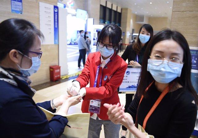 Un grupo de personas se desinfecta las manos con gel durante un evento de exposiciones en Shanghái.