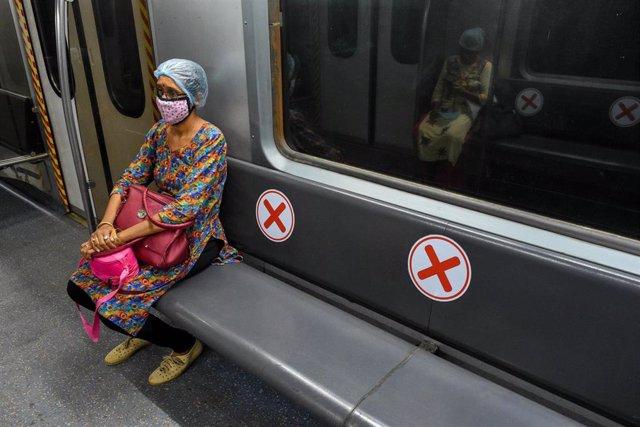 Una mujer con mascarilla en el metro de Calcuta