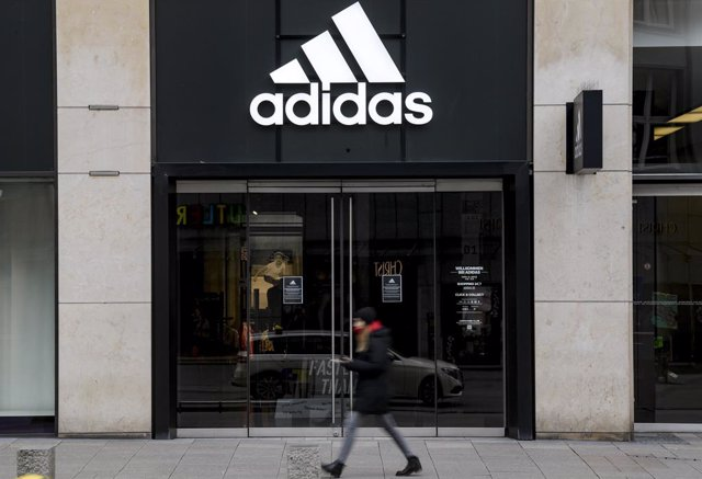 FILED - 01 April 2020, Hamburg: A woman walks in front of the closed entrance of a department store of the sporting goods manufacturer Adidas in downtown Hamburg. German sportswear company Adidas has ruled out its revenue decline in the third quarter by t