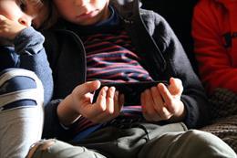 Pla mitjà d'un nen amb el telèfon mòbil a les mans. Imatge publicada el 8 de novembre del 2020. (Horitzontal)