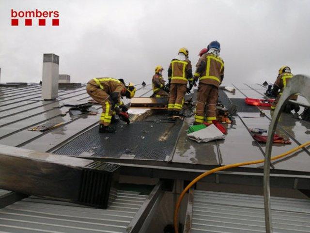 Pla mitjà dels Bombers treballant a la teulada de l'edifici afectat a Girona aquest dissabte 7 de novembre de 2020. (Horitzontal)