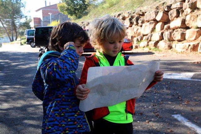 Pla mitjà de dos nens mirant-se el mapa. Imatge del 8 de novembre del 2020. (Horitzontal)
