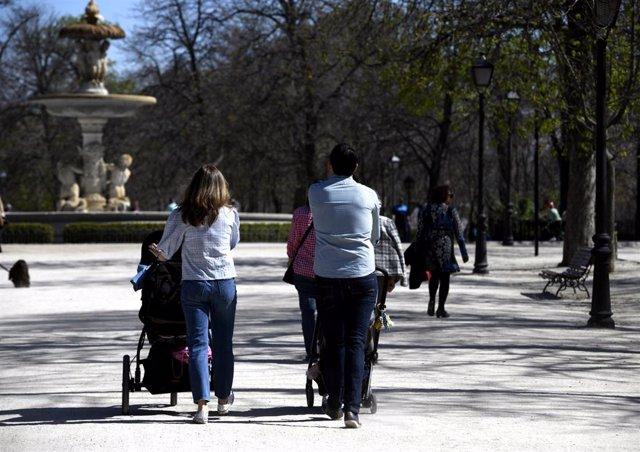 Unos padres pasean a sus hijos en sillitas de bebé por el Parque del Retiro, en Madrid (España).