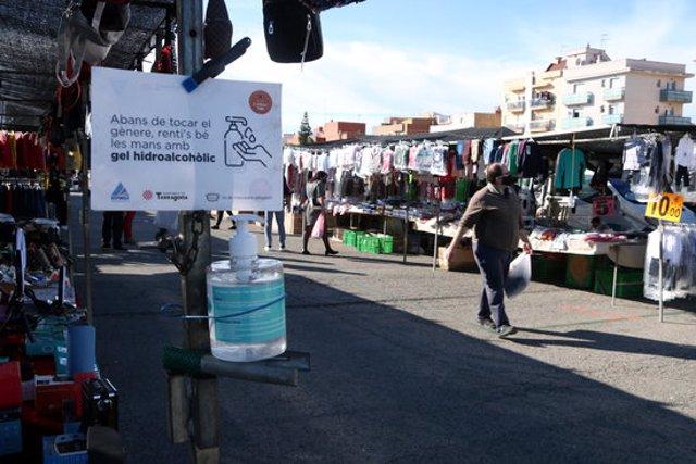 Pla tancat d'un cartell informatiu i de gel hidrolacòlit i de fons un comprador caminant al mercat de Bonavista en el segon cap de setmana de confinament municipal. Imatge del 8 de novembre del 2020 (Horitzontal).