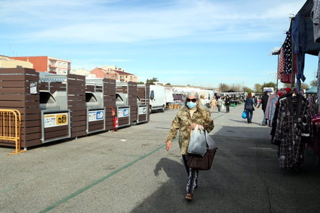 Pla general d'una dona caminant per davant d'una de les illes de contenidors de recollida selectiva al mercat de Bonavista de Tarragona. Imatge del 8 de novembre del 2020 (Horitzontal).