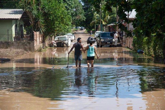 Una pareja anda por una calle anegada tras el paso de 'Eta' por Honduras.