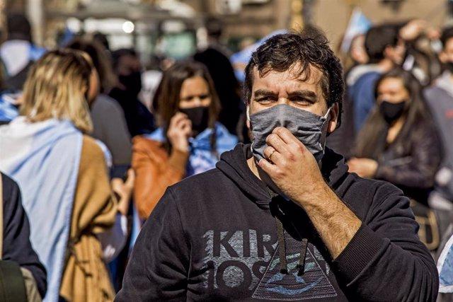 Un hombre con mascarilla pasea por las calles de Buenos Aires en plena crisis sanitaria provocada por la COVID-19.