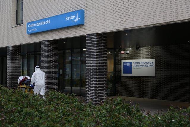 Un sanitario protegido con un traje, guantes y mascarilla, sale con una camilla de un centro sanitario en Vitoria