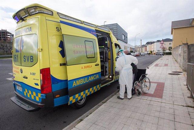 Un trabajador sanitario totalmente protegido ayuda a subir a la ambulancia a un anciano de la residencia de ancianos de San Cibrao donde se ha originado un brote de Covid-19.