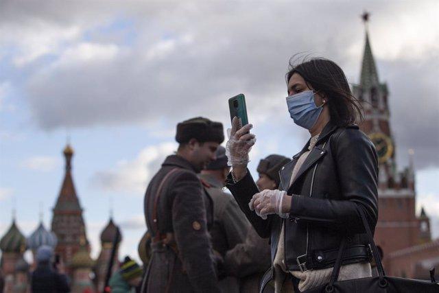 Una mujer con mascarilla se fotografía en la Plaza Roja de Moscú