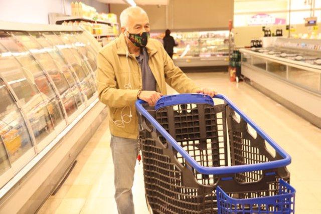 Pla obert d'un home amb un carro d'un supermercat mentre a través dels auriculars escolta 'Audioguia per a supermercats en temps de pandèmia' l'11 de novembre de 2020 (Horitzontal)
