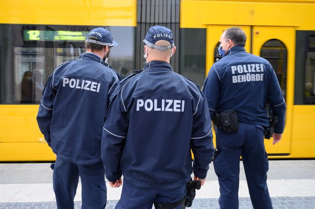 19 October 2020, Saxony, Dresden: (L-R) Policemen Andre Richter, Gabor Schulz, and Martin Mauthner stand in front of a tram at a stop on Postplatz as part of an operation to check the passengers' compliance with mask wearing obligations on public transpor