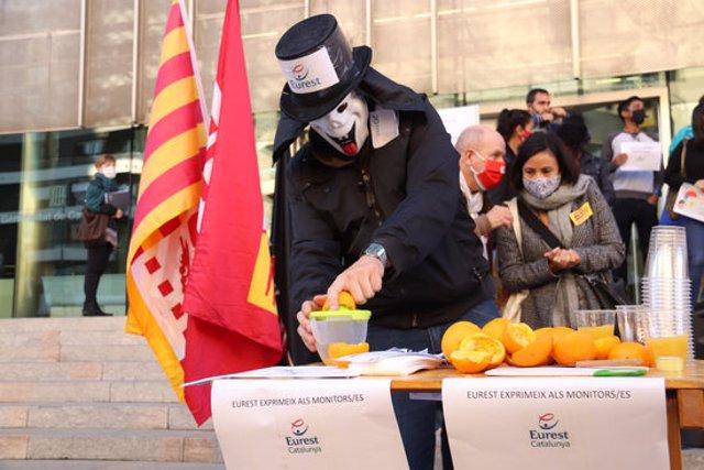 Pla obert d'un home disfressat fent suc de taronja que simbolitza l'empresa Eurest exprimint els seus treballadors en una concentració a Girona l'11 de novembre de 2020 (Horitzontal)