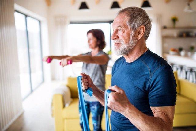 Pareja de personas mayores haciendo ejercicio en casa.