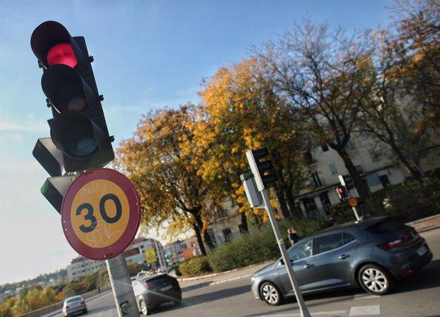 Varios coches circulan al lado de una señal de tráfico en una vía de la capital el mismo día en que han aprobado la reducción de la velocidad hasta 20km/h en las ciudades y la pérdida de seis puntos por usar el móvil, en Madrid, (España), a 10 de noviembr