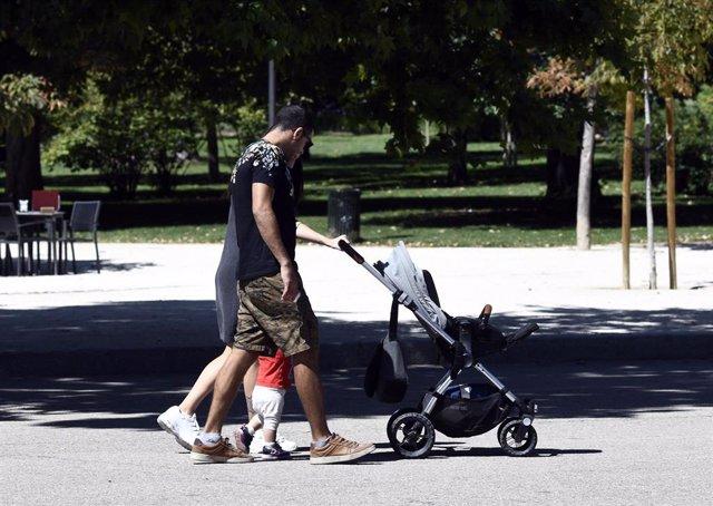 Una pareja y su bebé empujan el carrito en un parque de Madrid.